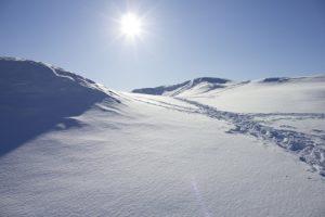 Footprints in snow along a mountain ridge.
